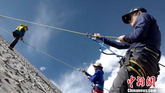 """西藏将于今年11月1日开启新一轮""""冬游西藏""""活动,攀登雪山受游客青睐。图为游客在西藏学习登山技巧。 贡桑拉姆 摄"""